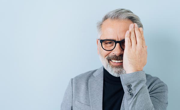 happy middle-aged man with eyeglasses looking at camera while covering his right eye with his hand