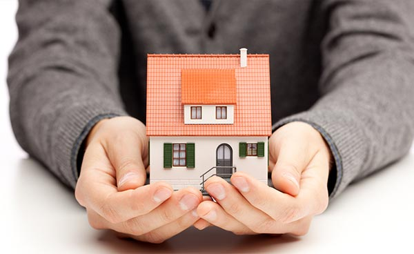 Man holding a small model of a house in his hands