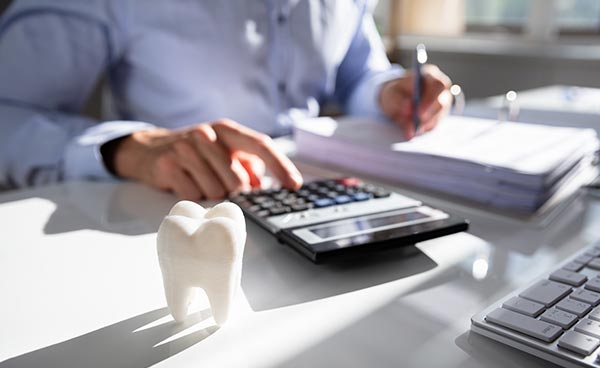 dentist with paperwork and calculator