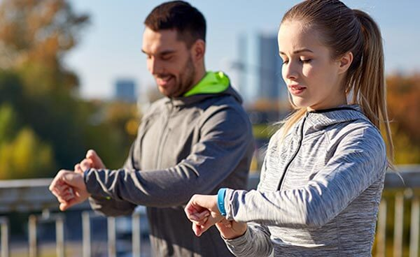 Two runners looking at their fitness activity trackers